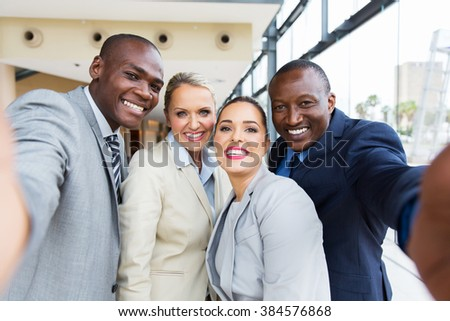 successful multiracial business team taking selfie together - stock photo