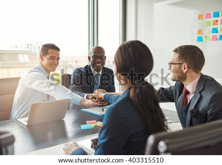 Successful multiracial business team working together affirm their commitment by linking hands across an office table during a meeting - stock photo