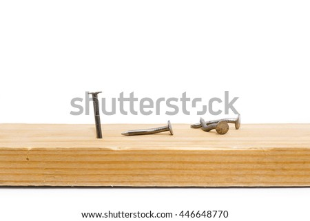 Successful nail, rivet hammered into a wooden piece, surrounded by crooked, broken nails, rivets