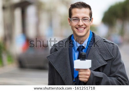 successful news reporter working in a cold weather outdoors - stock photo