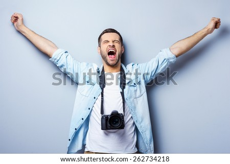 Successful photographer. Happy young man with digital camera keeping arms raised and eyes closed while standing against grey background - stock photo