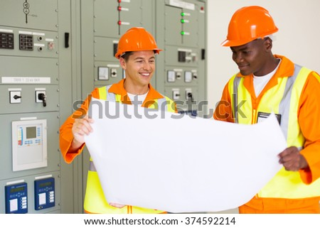 successful power company technical co-workers holding blueprint in control room - stock photo