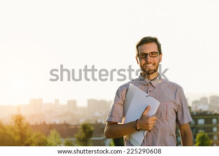 Successful professional casual man walking outside against city background. Happy smart looking person holding folder and smiling. - stock photo