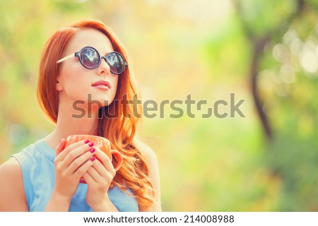 Successful redhead girl with cup in the autumn park. - stock photo