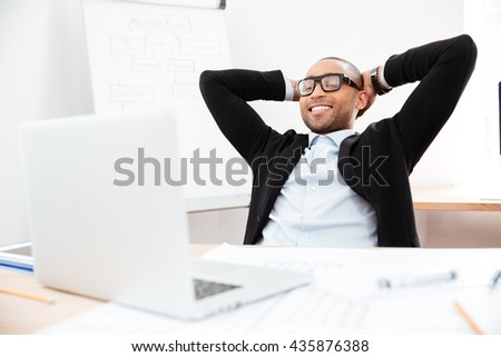 Successful relaxed young businessman sitting back in his chair with hands clasped behind his neck - stock photo