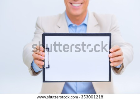 Successful results. Smiling businessman is upholding his clipboard and showing records. - stock photo