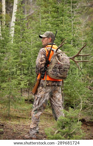 successful rifle hunter hiking through woods - stock photo