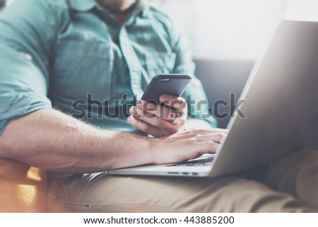 Successful Risk Manager working Laptop modern Interior Design Loft Office.Men work Vintage Sofa,Using contemporary Smartphone Hand Calling.Blurred Background.Business Startup Idea Process.Closeup - stock photo