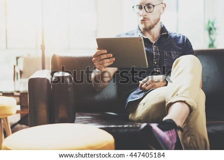 Successful Risk Trader working Laptop modern Interior Design Loft Office.Men work Vintage Sofa,Using contemporary tablet Hand Texting.Blurred Background.Business Startup Idea Process.Film effect - stock photo