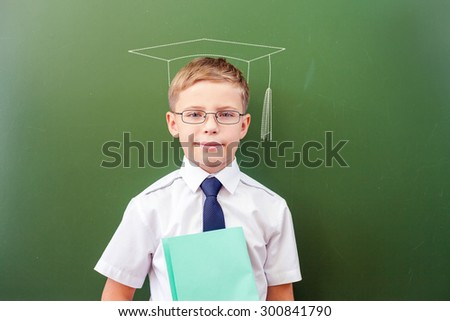 Successful schoolboy standing near the blackboard in a school classroom, dressed in a school uniform, pictured hat by chalk and sunglasses - stock photo