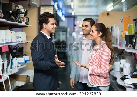Successful seller and smiling buyers at household appliances section of supermarket - stock photo