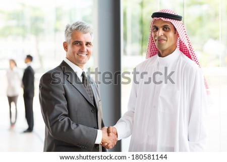 successful senior businessman handshake with Arabian partner - stock photo