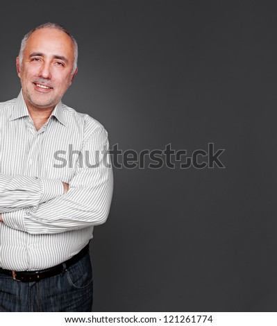 successful senior man with folded hands standing near empty copyspace