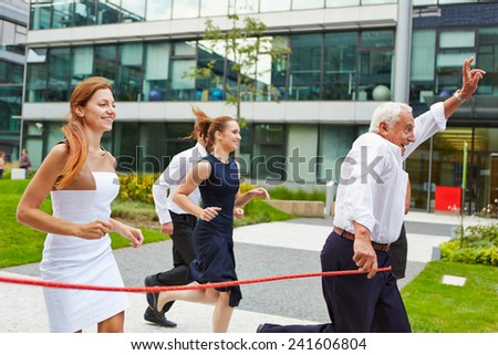 Successful senior manager winning a run with his business team at the finish line - stock photo