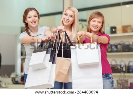 Successful shopping.  Three smiling women stretching out shopping bags copyspace with the view of the shop on the background - stock photo