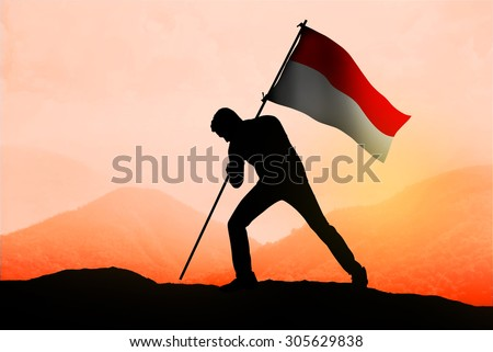 Successful silhouette man waving Indonesian flag on top of the mountain peak - stock photo