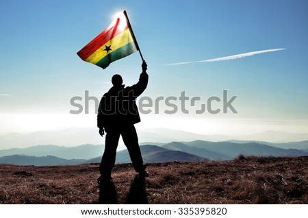successful silhouette man winner waving Ghana flag on top of the mountain peak - stock photo