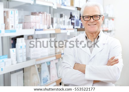 Successful small business owner. Cheerful senior pharmacist smiling to the camera while working at his drugstore profession doctor chemist pharmaceuticals medical health concept