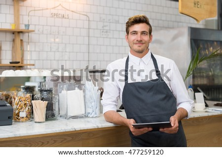 Successful small business owner holding digital tablet and looking at camera. Happy smiling waiter with apron and digital tablet leaning on counter. Portrait of young entrepreneur of coffee shop.