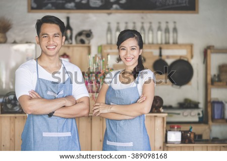 Successful small business owner proudly standing in front of their cafe - stock photo