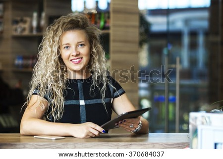 Successful small business owner standing at the bar and holding a tablet cancers