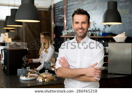 Successful small business owner standing with crossed arms with employee in background preparing coffee - stock photo