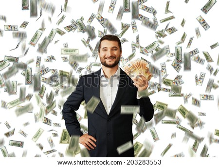 successful smiley businessman standing under money rain and holding euro