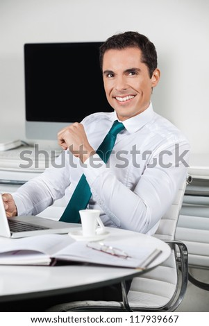 Successful smiling manager working with laptop in his office