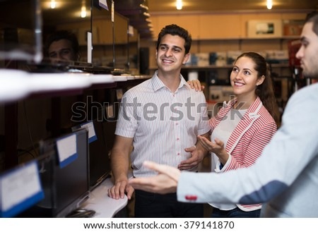 successful spanish consultant helping young couple to choose PC monitor