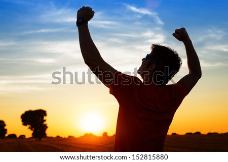Successful sportsman raising arms on golden sky back lighting sunset summer after cross running. Fitness male athlete with arms up celebrating goals after sport exercising and working out outdoors. - stock photo