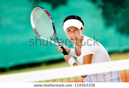 Successful sportswoman in sportswear playing tennis - stock photo