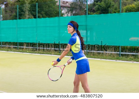 Successful sportswoman wearing a tenniswear prepares for the game on a court outdoor in summer or spring