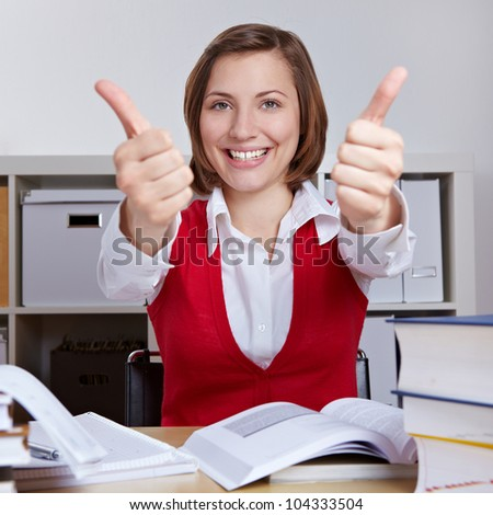 Successful student at desk with books holding both thumbs up - stock photo