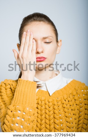 Successful stylish girl closes eyes with her hands, isolated in the studio - stock photo