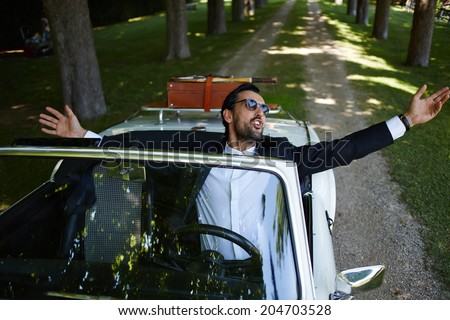 Successful stylish man with arms raised and feeling of freedom sitting behind the wheel of cabriolet classic luxury car, lifestyle and successful business concept
