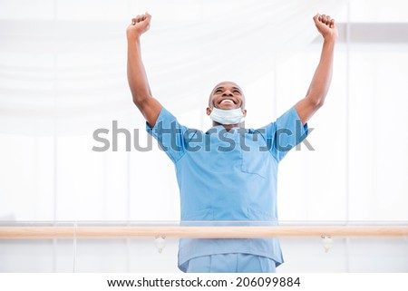Successful surgeon. Low angle view of happy young African doctor in blue uniform keeping arms raised and smiling - stock photo