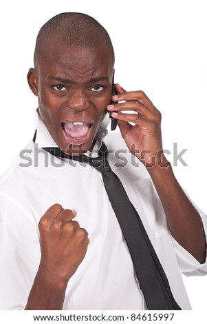 Successful surprised young handsome businessman with clenched fist using mobile phone - stock photo
