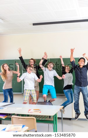 Successful Teacher and students jump in front of a blackboard with math work in a classroom or class school while lesson - stock photo