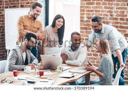 Successful team. Group of cheerful young people discussing something with smile and gesturing while leaning to the table in office - stock photo