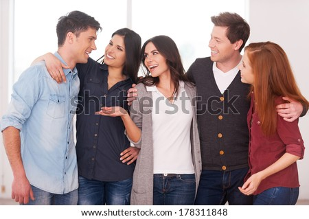 Successful team. Group of cheerful young people standing close to each other and communicating - stock photo