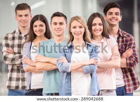 Successful team. Group of cheerful young people standing close to each other and smiling. - stock photo