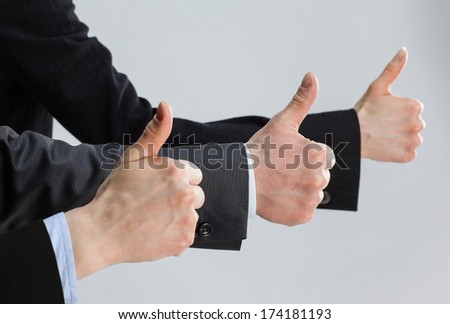 Successful team in dark suits showing thumbs up on grey background