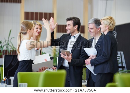 Successful team of business people giving high five in the office - stock photo