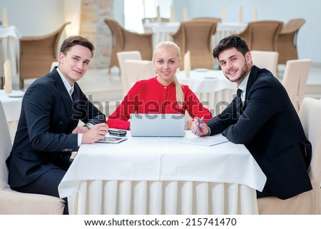 Successful team of three successful businessman discussing work at a laptop. Businesspeople in formal attire sitting in an office at a desk and looking into the camera in formalwear