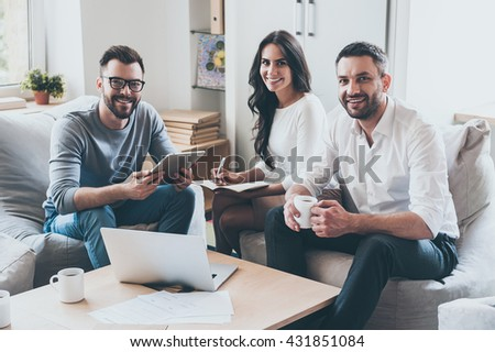 Successful team. Three confident business people in smart casual wear looking at camera and smiling while sitting together at the desk in office  - stock photo