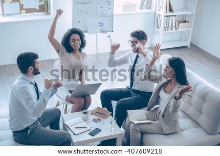 Successful team. Top view of group of four young people gesturing and looking happy while sitting on the couch at office   - stock photo