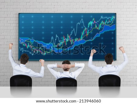 Successful traders in front of the forex screen  - stock photo
