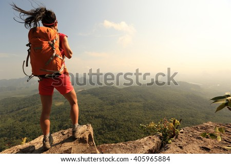 successful woman hiker enjoy the view on mountain top