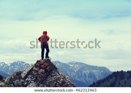 successful woman hiker enjoy the view on mountain top cliff