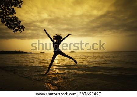 Successful woman jumping, dancing and having fun on sunset in beach Freedom and happiness concept Girl celebrating work out success